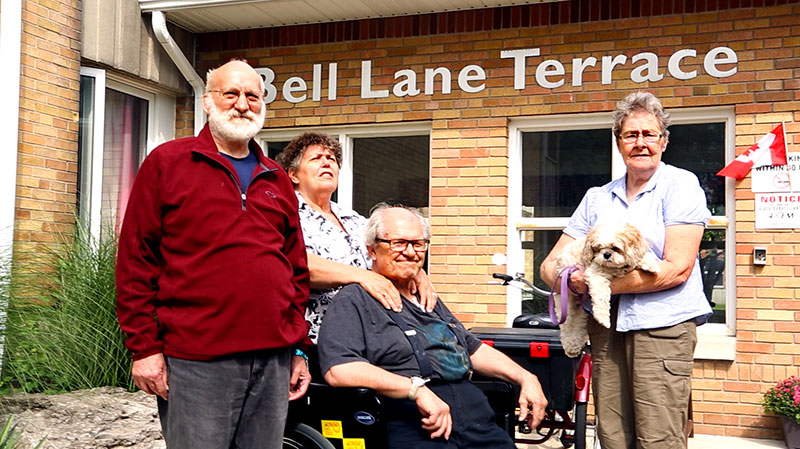 A group of tenants in front of the Bell Lane Terrace entrance.